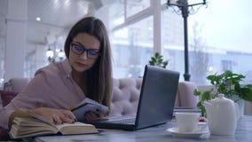 Het online onderwijs, meisje in oogglazen schrijft nota's in notitieboekje tijdens videopraatje op moderne netbookzitting bij lij stock footage