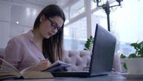 Het online onderwijs, studentenmeisje in oogglazen schrijft nota's in notitieboekje tijdens videopraatje op moderne netbookzittin stock footage