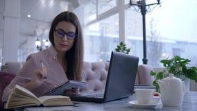 Het online onderwijs, vrouwelijke student las boek en schrijft nota's in notitieboekjezitting bij lijst met laptop stock videobeelden