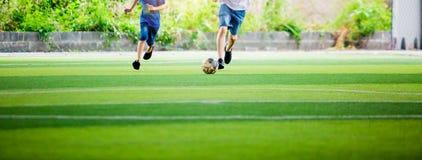 Het onscherpe de Jong geitjevoetbal en papa spelen bal bij kunstmatig gras royalty-vrije stock afbeelding