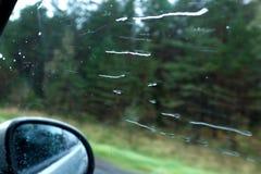 Het onscherpe patroon van kleurrijke motieregen laat vallen op het windscherm van de auto op een regenachtige dag een regendruppe stock foto's