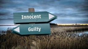 Het Onschuldige van het straatteken tegenover Schuldig stock foto