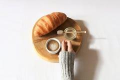 Het ontbijt in bedvlakte lag De holdingskop van de vrouwenhand van koffie, houten besnoeiing met vers croissant en honing in bed  Stock Afbeeldingen