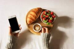 Het ontbijt in bedvlakte lag Vrouwenhanden die kop van koffie en telefoon, houten besnoeiing met vers croissant en aardbei in bed Royalty-vrije Stock Fotografie