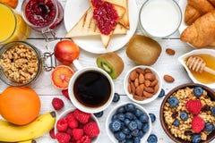 Het ontbijt diende met koffie, jus d'orange, toosts, croissants, graangewassen, melk, noten en vruchten Uitgebalanceerd dieet stock afbeelding