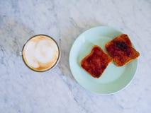Het ontbijt met cappuccino en het geroosterde brood met jam dienden op een marmeren lijst Royalty-vrije Stock Foto