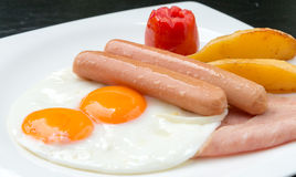 Het ontbijt met gebraden ei, worsten, tomaat, aardappels braadde op witte plaat Stock Afbeelding
