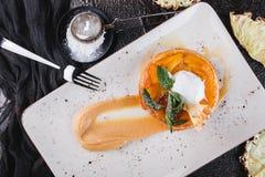 Het ontbijt met heerlijke appelstrudel met ananas, jam, roomijs versierde met munt en poederde suiker op lichte plaat stock foto's