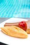 Het ontbijt met omelet, worsten, tomaat, aardappels braadde op witte plaat Stock Afbeelding