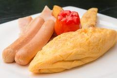 Het ontbijt met omelet, worsten, tomaat, aardappels braadde op witte plaat Stock Fotografie