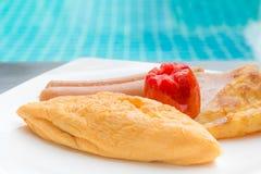 Het ontbijt met omelet, worsten, tomaat, aardappels braadde op witte plaat Royalty-vrije Stock Foto's