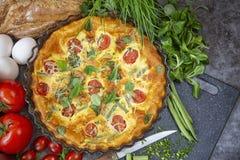 Het ontbijt Omelet in de oven met slabonen, tomaten, kruiden en kaas Voedsel op donkere achtergrond stock foto