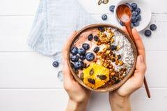 Het ontbijt smoothie werpt met chiapudding, bessen en granola in kokosnotenshell op witte houten achtergrond stock afbeelding