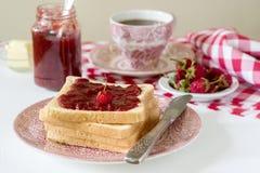 Het ontbijt van broodtoosts met boter en de aardbei-rabarber blokkeren, gediend met thee Rustieke stijl royalty-vrije stock afbeelding