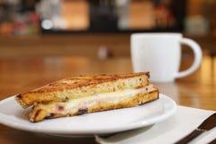 Het ontbijt van de de sandwichclub van de Wholdtarwe en de kop van de onduidelijk beeldkoffie erachter stock afbeeldingen