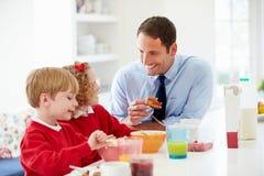 Het Ontbijt van vaderand children having in Keuken samen Stock Afbeeldingen