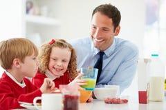 Het Ontbijt van vaderand children having in Keuken samen Royalty-vrije Stock Foto's