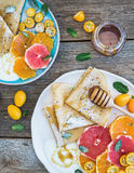 Het ontbijtreeks van de de lentevitamine Dun omfloerst of pannekoeken met verse grapefruit, sinaasappel, kumquat, honings, room e stock fotografie