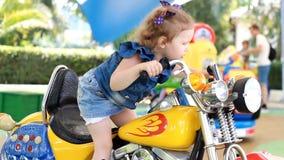 Het ontevreden en droevige kindmeisje berijdt een elektrische motorfiets in het park voor vermaak stock footage