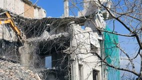 Het ontmantelen van het huis met zware machines Backhoe vernietigt het huis, stuk voor stuk ontmantelend het stock footage