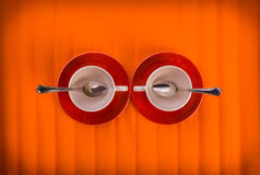 Het ontmoeten van twee witte lege koppen met thee lepelt hierboven, op rode platen over oranje kleurenachtergrond, mening van Stock Afbeelding