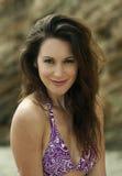 Het ontspannen aantrekkelijke donkerbruine meisje die purpere bikini dragen stelt op de rots door het overzees Stock Afbeeldingen