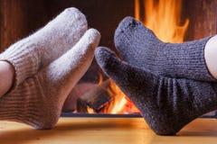 Het ontspannen bij de comfortabele open haard op de winteravond Stock Afbeeldingen