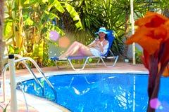 Het ontspannen in de tuin door de pool Stock Foto