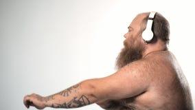 Het ontspannen dikke gebaarde kerel bewegen zich dient ritme van melodie in stock video