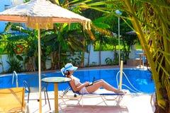 Het ontspannen door de pool Stock Foto