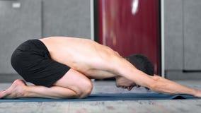 Het ontspannen geschiktheid mannelijke het praktizeren yoga uitrekkende ontspannen op mat binnen volledig schot stock footage