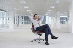 Het ontspannen het Nieuwe Bureau van Zakenmanon chair in Stock Fotografie