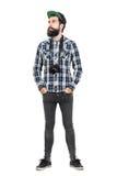 Het ontspannen hipster dient dragen van zwarte dslrcamera over hals met zakken in Royalty-vrije Stock Foto's