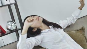Het ontspannen meisje zit op bank, en langzaam rek omhoog lui handen uit en geeuwend, stock footage