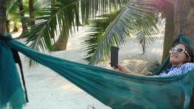 Het ontspannen meisje in zonnebril maakt selfie met Mobiel Telefoon verkopen liggend in Hangmat tussen palmen Langzame Motie stock video