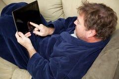 Het ontspannen met Tabletpc stock afbeelding