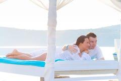Het ontspannen op luxe wit bed bij het overzees Royalty-vrije Stock Afbeelding