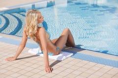 Het ontspannen op poolside. Achtermening van mooi blond haar wome stock afbeelding