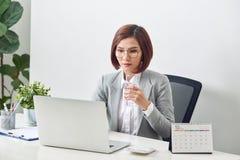 Het ontspannen rijpe glas van de onderneemsterholding van water en het werken aan haar laptop in het bureau royalty-vrije stock afbeelding