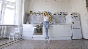 Het ontspannen sexy blonde stellen op keuken in ochtend actie Sexy jonge blondevrouw in de keuken thuis royalty-vrije stock afbeelding