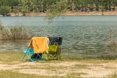 Het ontspannen stoelen op het water stock foto