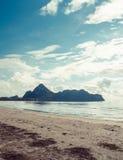 Het ontspannen strand van het zeegezicht het tropische paradijs met wit zand en eiland in het overzees royalty-vrije stock afbeeldingen