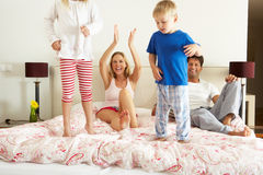 Het Ontspannen van de familie samen in Bed Stock Fotografie