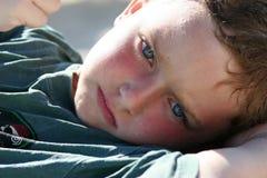 Het ontspannen van de jongen op strand Stock Foto's