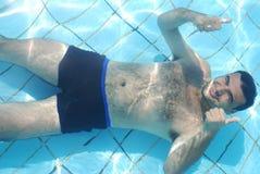 Het ontspannen van de mens bij de bodem van zwembad Royalty-vrije Stock Afbeelding