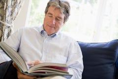 Het ontspannen van de mens met boek in woonkamer Stock Afbeeldingen