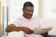 Het ontspannen van de mens met krant het glimlachen Stock Foto