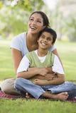 Het ontspannen van de moeder en van de zoon in park stock afbeeldingen