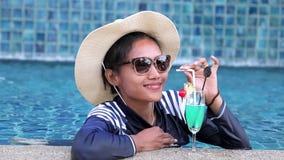 Het ontspannen van de vrouw bij de pool stock videobeelden