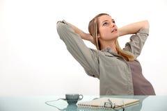 Het ontspannen van de vrouw bij haar bureau Royalty-vrije Stock Fotografie